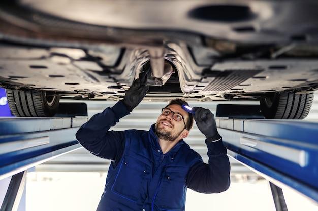 자동차의 기술 검사. 워크샵에서 자동차 서비스. 파란색 유니폼을 입은 남자가 차고의 차 아래에 서서 차축을 확인합니다. 손전등으로 섀시를 비 춥니 다.