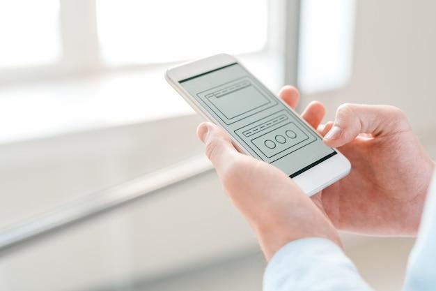 Технические схемы в смартфоне, который держит молодой бизнесмен, просматривая их и анализируя