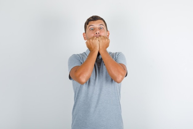 Technical service man biting his fists in grey t-shirt and looking nervous