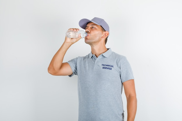 Technical service man drinking water in grey t-shirt with cap
