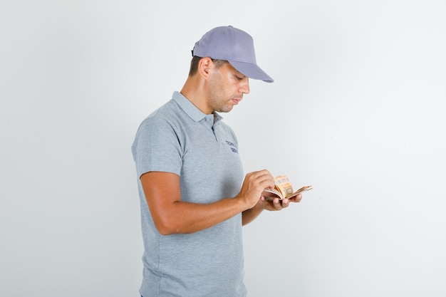 Technical service man in grey t-shirt with cap counting euro banknotes