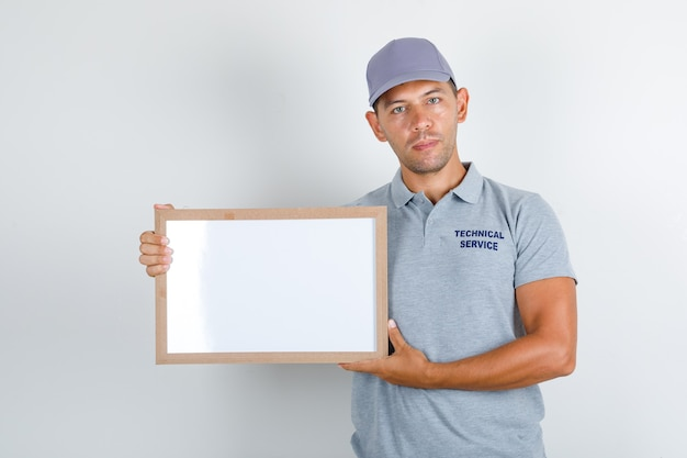 Technical service man holding white board in grey t-shirt with cap, front view.