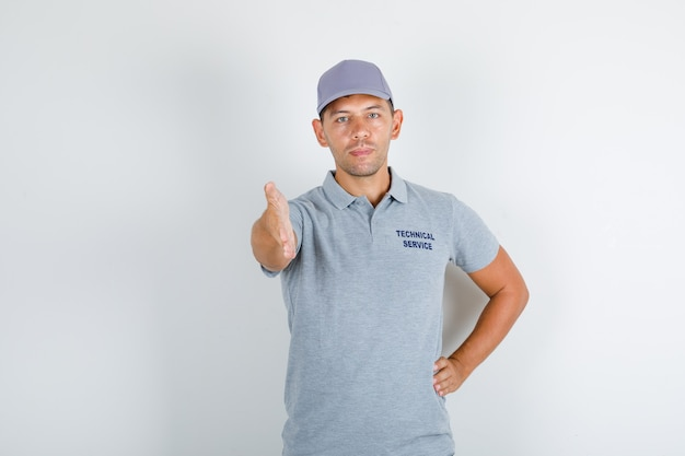 Человек технической службы в серой футболке с кепкой, протягивающей руку для рукопожатия