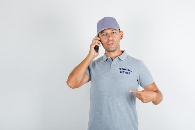 Человек технической службы в серой футболке с кепкой держит смартфон и показывает себя