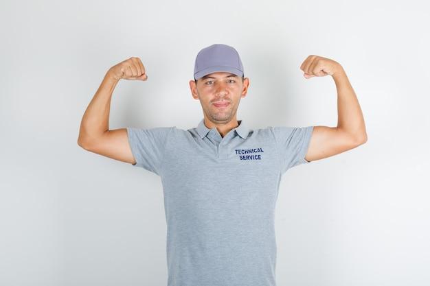 Человек технической службы в серой футболке с кепкой, показывающий мускулы и сильный вид