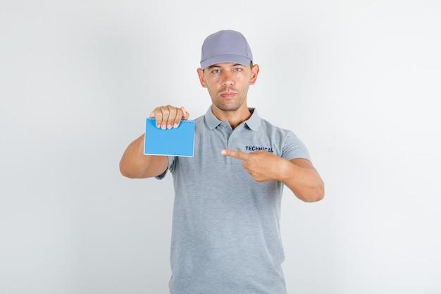Человек технической службы указывая пальцем на ноутбук в серой футболке с кепкой