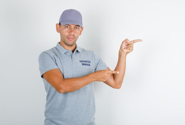 Technical service man pointing fingers away in grey t-shirt with cap and looking positive