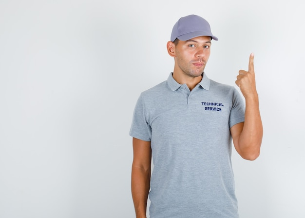 Technical service man showing finger up in grey t-shirt with cap
