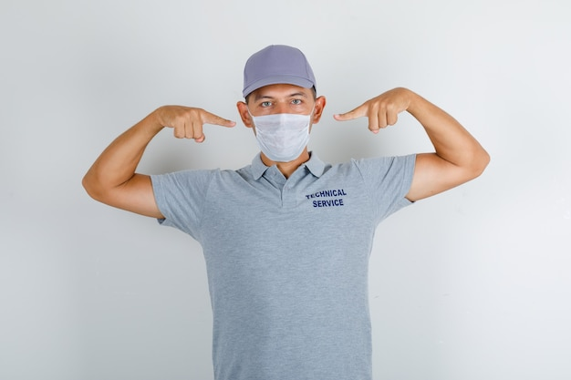 Technical service man showing medical mask in grey t-shirt with cap and looking careful