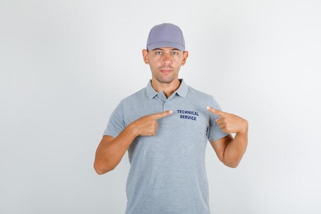 Человек технической службы показывает текст на униформе в серой футболке с кепкой