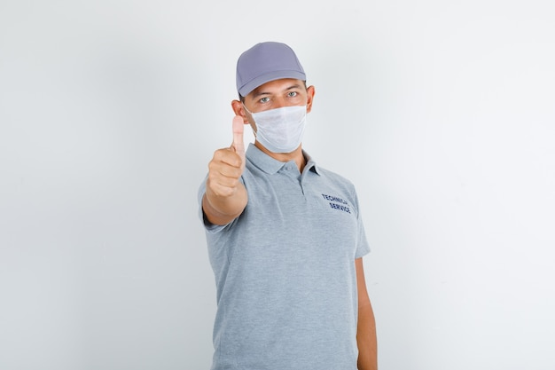 Technical service man showing thumb up in grey t-shirt with cap and medical mask and looking careful