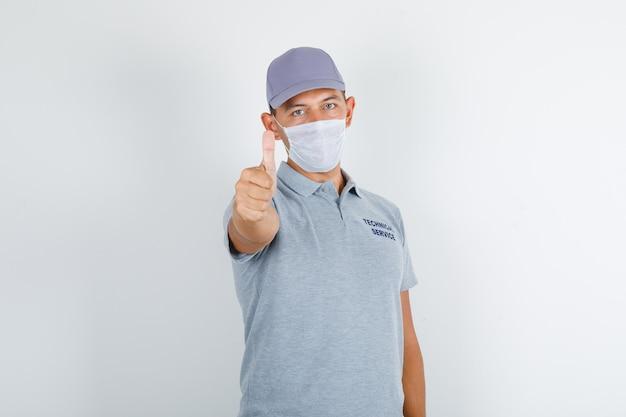 テクニカルサービスの男性がキャップと医療マスク付きのグレーのtシャツに親指を現して注意深く見て