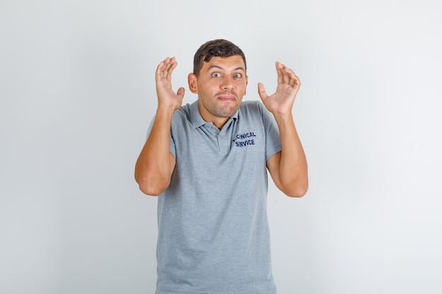 テクニカルサービスの男性が開いた手のひらで肩をすくめて灰色のtシャツを着て、おかしい