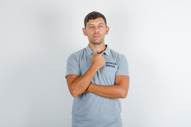 Technical service man standing with clenched fist in grey t-shirt and looking serious