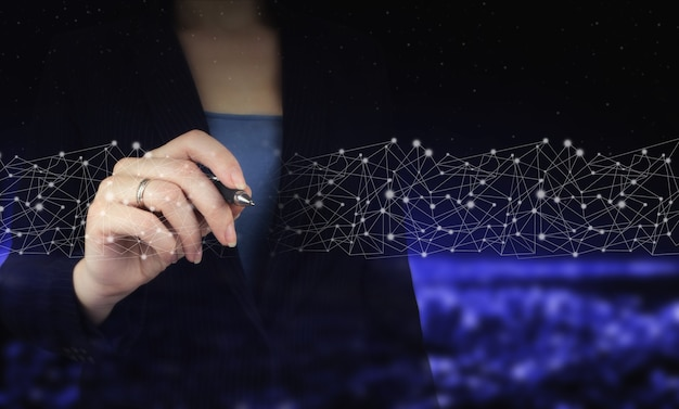 Technical support customer service business technology internet. hand holding digital graphic pen and drawing digital hologram wave sign on city dark blurred background. innovation, big data.