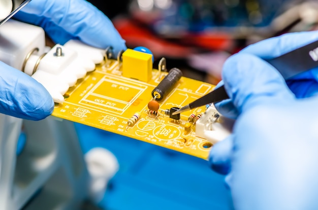 Technical support worker drops the fee pcb. soldering iron. tweezers