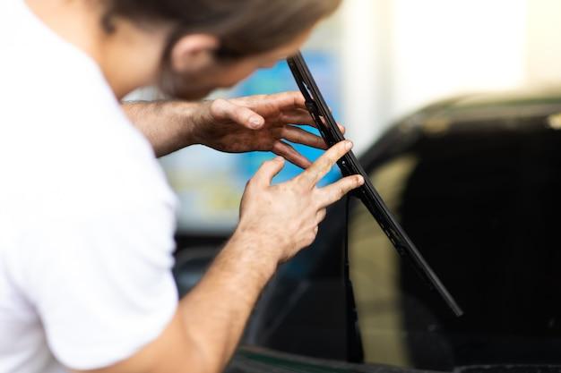 Техник и механик меняют дворники на автомобильной станции. обслуживание автомобилей и концепция гаража автосервиса.