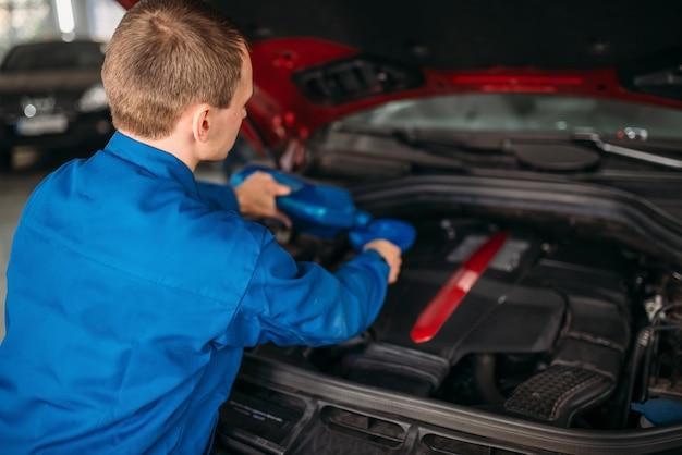 Техник меняет масло в двигателе автомобиля