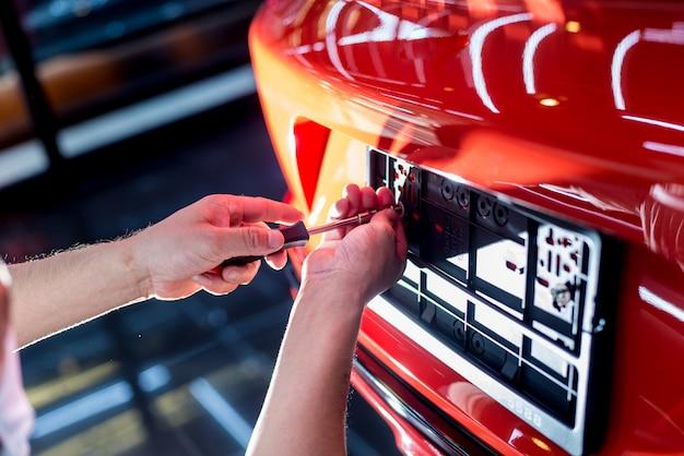 Техник меняет номерной знак автомобиля в сервисном центре.
