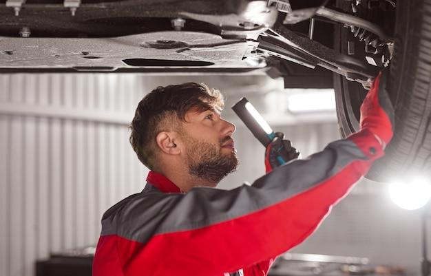 Техник, проверяющий шасси автомобиля в мастерской