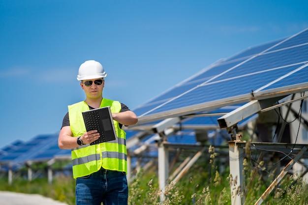 Техник, проверяющий эффективность солнечной панели на солнечной электростанции.