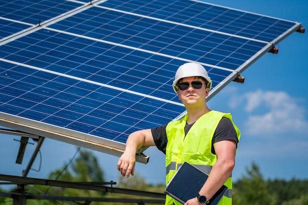 기술자는 태양광 발전소에서 태양 전지판의 효율성을 확인합니다.