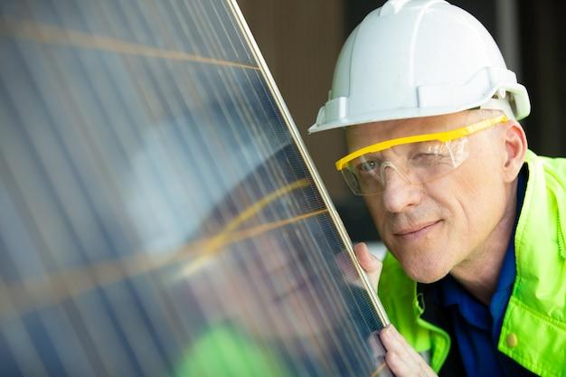 Техник, проверяющий на панели управления солнечных батарей.