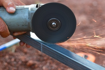 Technician cutting steel with tool in the workplace.