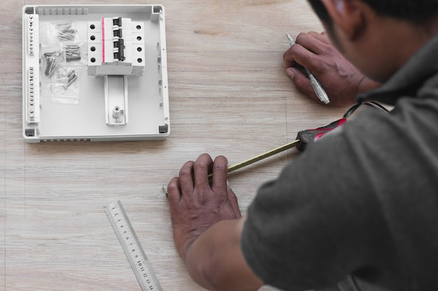 Technician design and installing circuit breakers at electricity distribution board