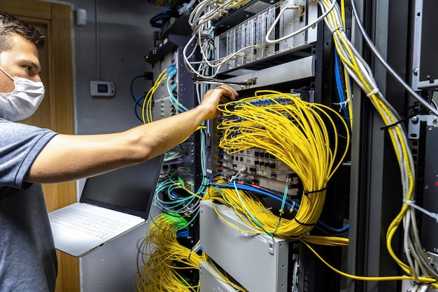 Technician engineer fixing problem with servers and data in cables room
