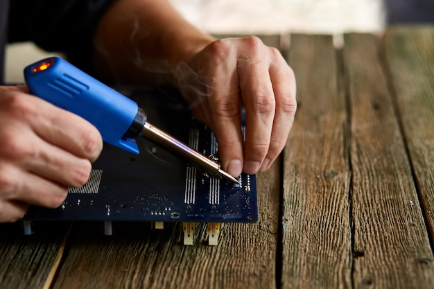 Technician or engineer is focused on repairing circuit board with soldering iron.