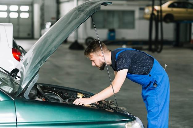 Техник, фиксирующий двигатель автомобиля в гараже