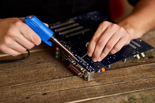 Technician focusing on repairing the circuit board with a soldering iron