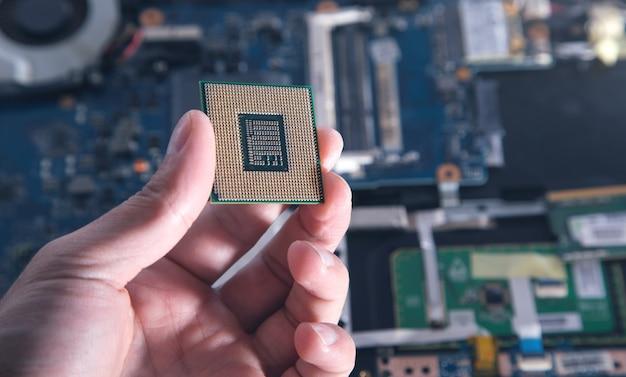Pcのcpuプロセッサを持っている技術者の手。