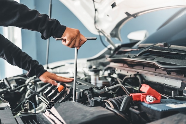 Technician hands of car mechanic working in auto repair