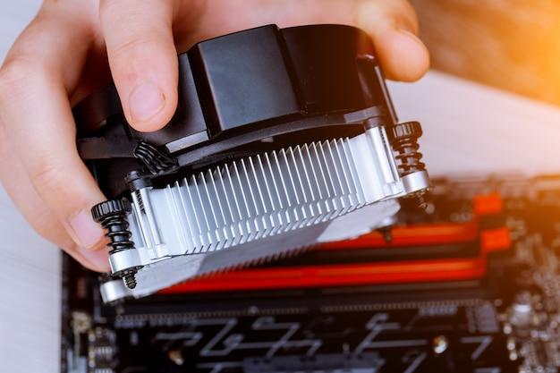 Technician hands installing cpu cooler fan on a computer pc motherboard