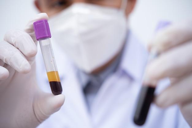 病院の実験室の試験管に遠心分離された血液サンプルを保持している技術者