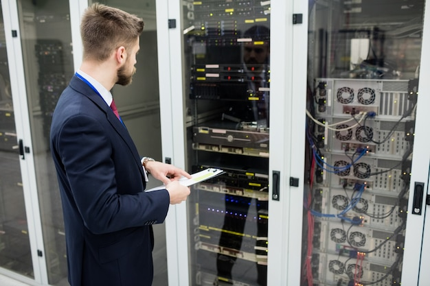 Technician holding clipboard while analyzing server