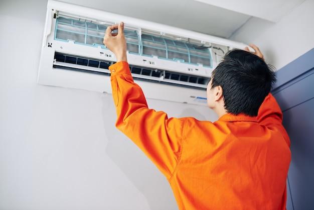 아파트 또는 사무실에 컨디셔너를 설치하는 주황색 작업복의 기술자