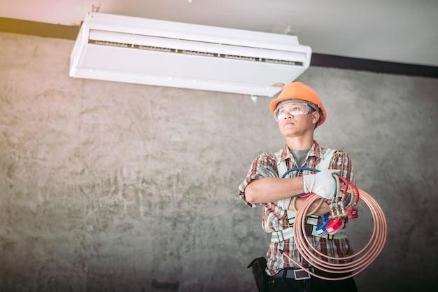 標準的な安全服の技術者エアコンのコンプレッサーをチェックしようとしています
