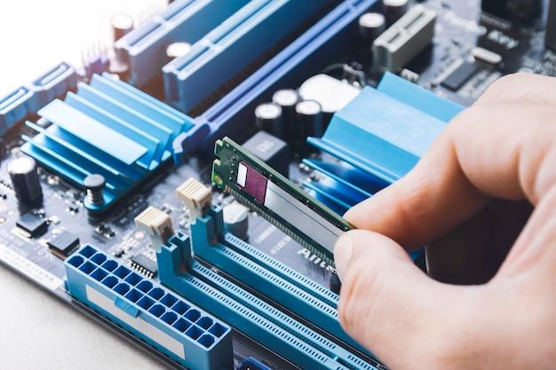 Technician install new ram (random-access memory) to memory slot on computer motherboard