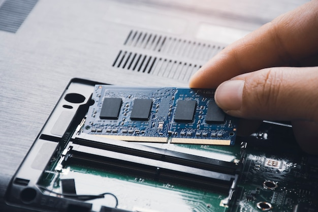 Technician install new ram randomaccess memory to memory slot on laptop motherboard