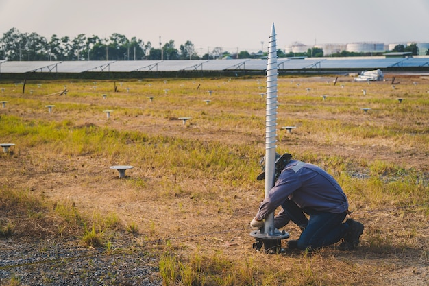 Technician installing ground screw for mounting structure of solar panel at solar farm