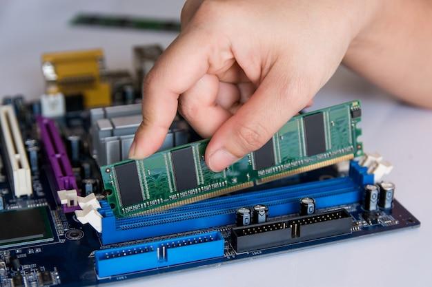 Technician installing ram stick (random access memory) to socket on motherboard