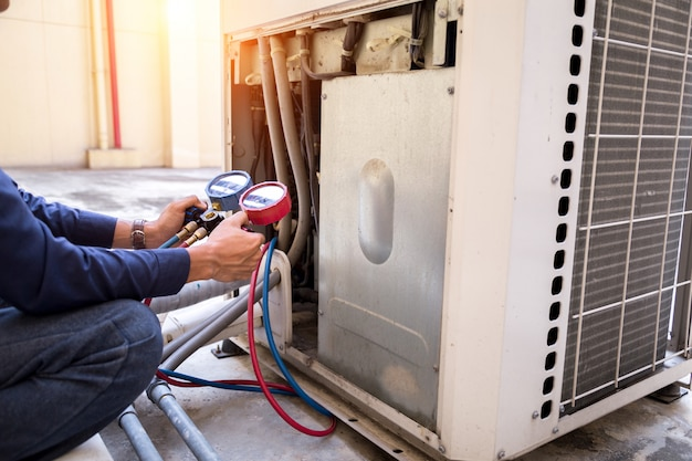 Technician is checking air conditioner measuring equipment for filling air conditioners.