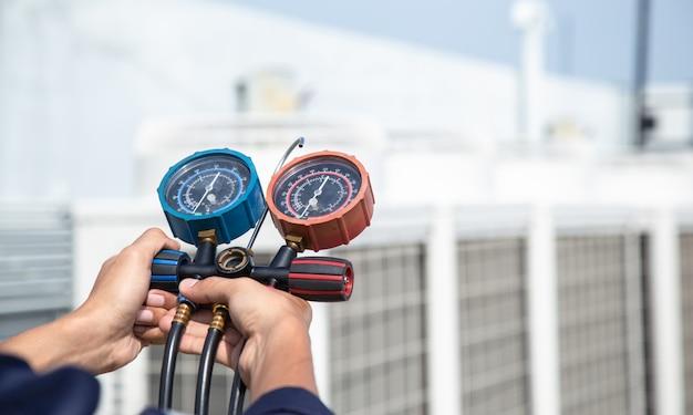 기술자가 에어컨을 점검하고, 에어컨을 채우기 위한 측정 장비, 에어컨 서비스 및 유지 보수를 하고 있습니다.