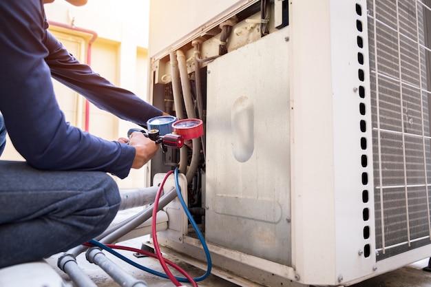 Техник проверяет кондиционер, измерительное оборудование для заправки кондиционеров.