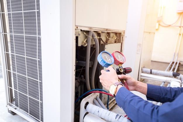 Техник проверяет оборудование для измерения кондиционера для заполнения кондиционеров.