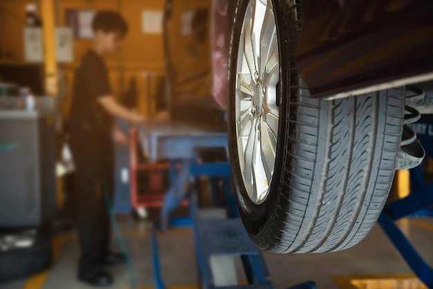 Technician is inflate car tire, car maintenance service transportation safety