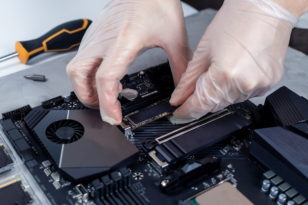 Technician is installing new fast high capacity ssd drive on the computer motherboard